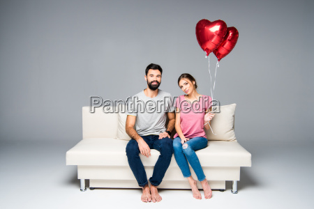 couple, sitting, on, couch, with, red - 20558157