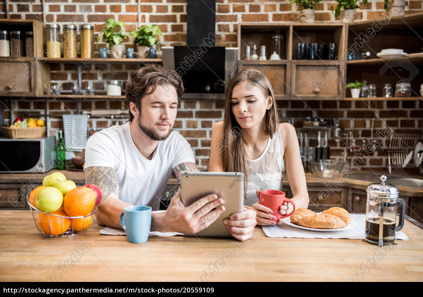 couple, using, digital, tablet, at, kitchen - 20559109