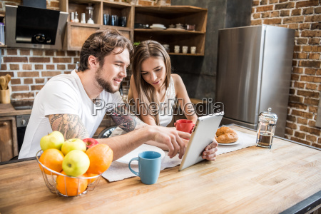 couple, using, digital, tablet, at, kitchen - 20559111