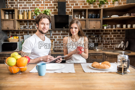 couple, using, digital, tablet, at, kitchen - 20559113