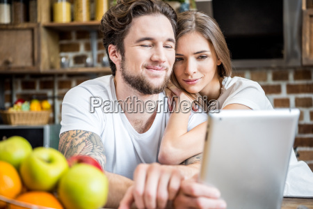 couple, using, digital, tablet, at, kitchen - 20559123