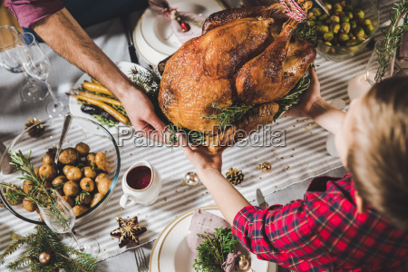 father, and, son, holding, roasted, turkey - 20559411