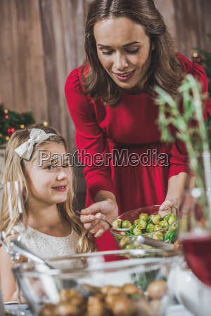 woman, putting, brussel, sprouts, on, plate - 20559385