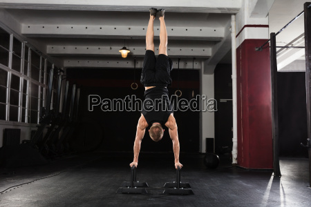 man, doing, handstand, on, parallel, bar - 20562923