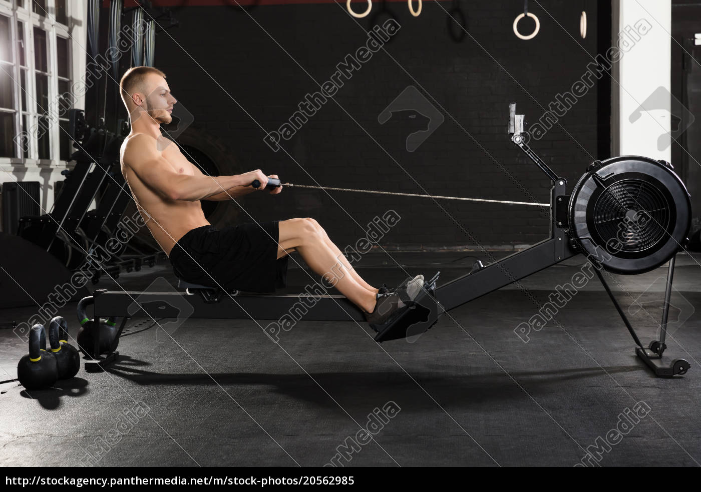 young, man, exercising, with, row, machine - 20562985