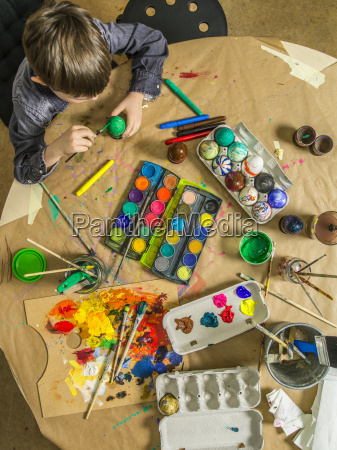 young boy decorating easter eggs