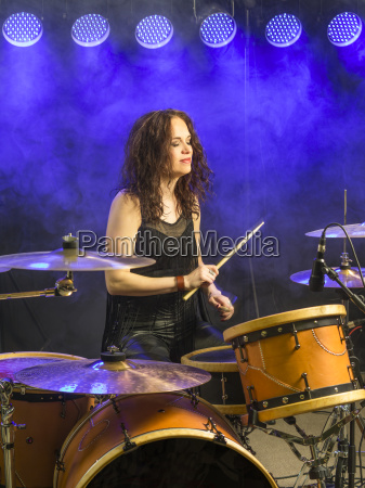 beautiful woman playing drums on stage