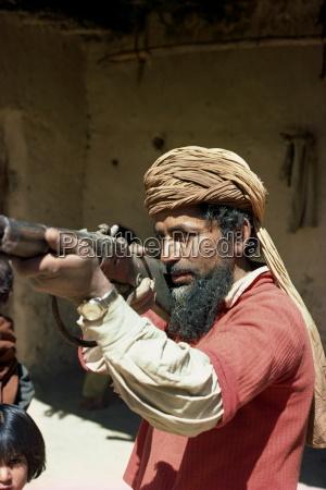 pathan man aiming rifle near ziarat