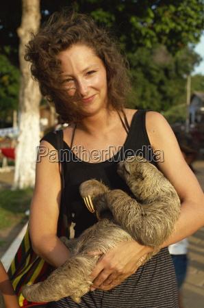 lady cuddles three toed sloth alter