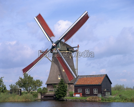 thatched windmill on the canal at