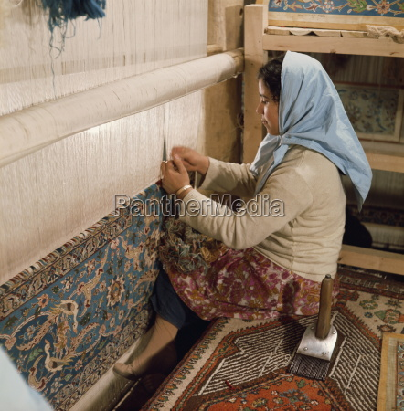 young woman weaving carpet on loom