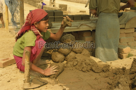 child labour young girl moulding lumps
