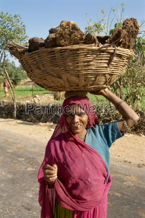 woman carrying dung pats used for