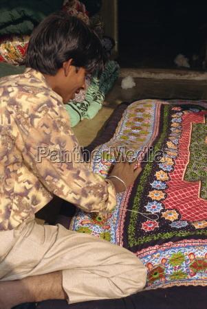 young man sewing quilt dhariyawad rajasthan