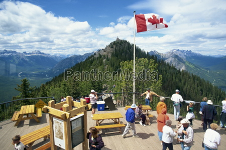tourists beneath the canadian flag on
