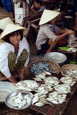 women in straw hats selling fish