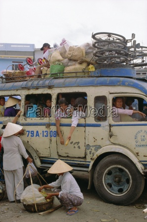 crowded bus with bicycles sacks and