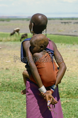 teenage masai mother carrying her child