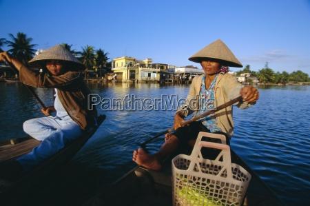 women paddling canoes on thu bon