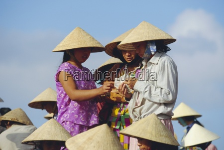 women in conical hats counting money