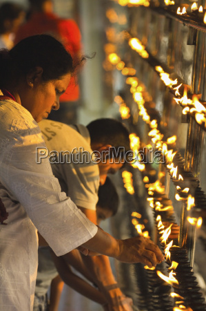 devotee lighting candles at sunset in