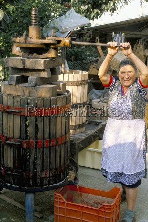 a local winemaker pressing her grapes