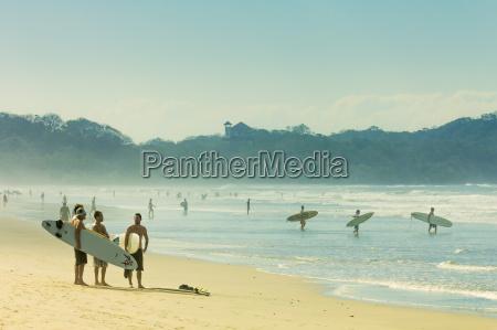 surfers on playa guiones beach nosara