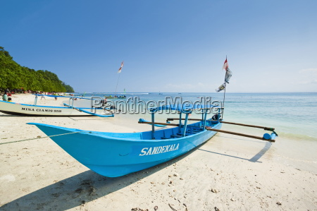 outrigger boats on beautiful white sand