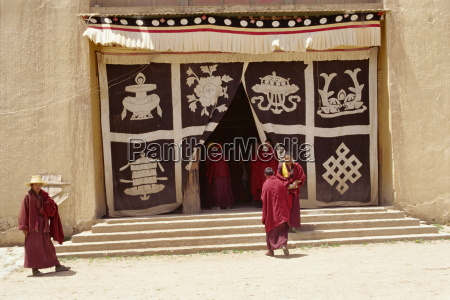 lamas at monastery entrance which is