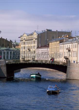 small boats pass under a bridge