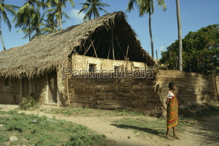 child stood before traditionally built home