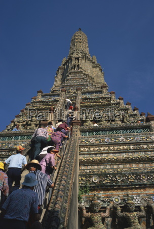 tourists climb the steps of wat