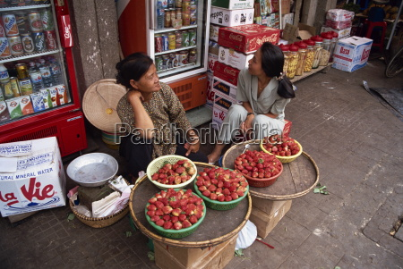 two women street vendors selling strawberries
