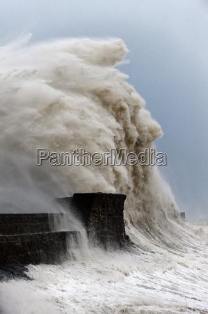 huge waves crash against the harbour