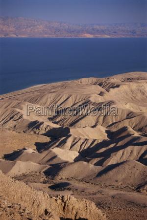 arid hills on shore of dead