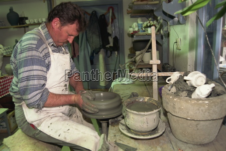 man working on potters wheel ceramics