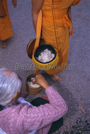 novice monk receiving alms in the