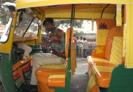 rickshaw owner sitting in his newly