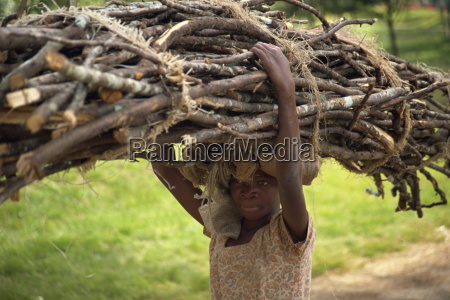 young girl carrying large bundle of