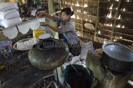young woman peparing rice noodles at