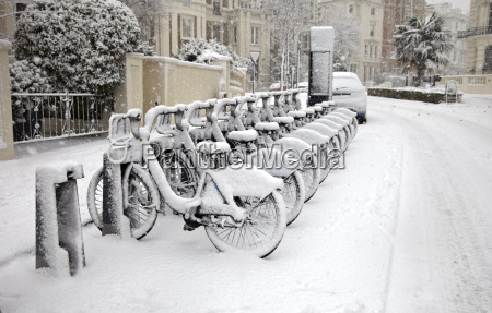 rows of hire bikes in snow