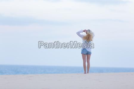 woman on sandy beach in white