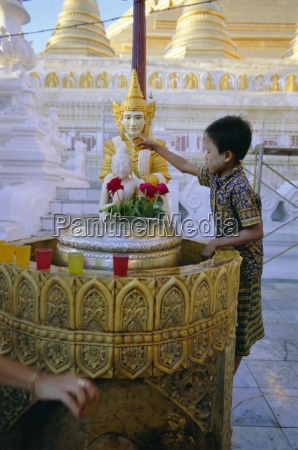 a boy places offerings to the