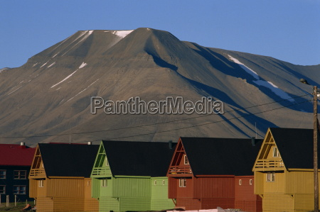 row of painted wooden miners huts