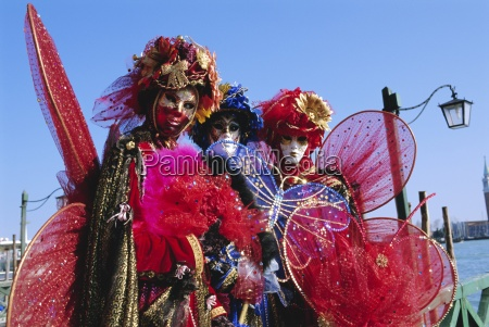 people wearing masked carnival costumes venice