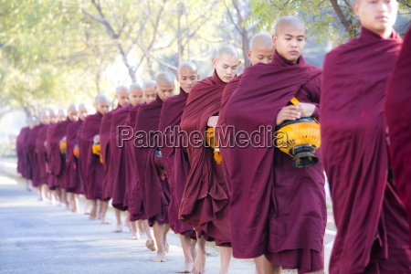 buddhist monks walking along road to