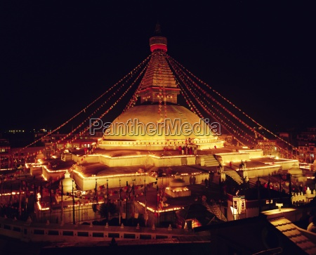 buddhist stupa lit by candles at