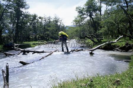 backpacker crosses log bridge on circuit