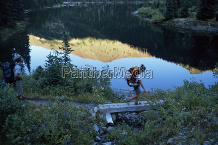 backpacker crossing bridge olympic national park