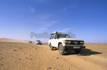 jeeps driving through desert erg murzuq